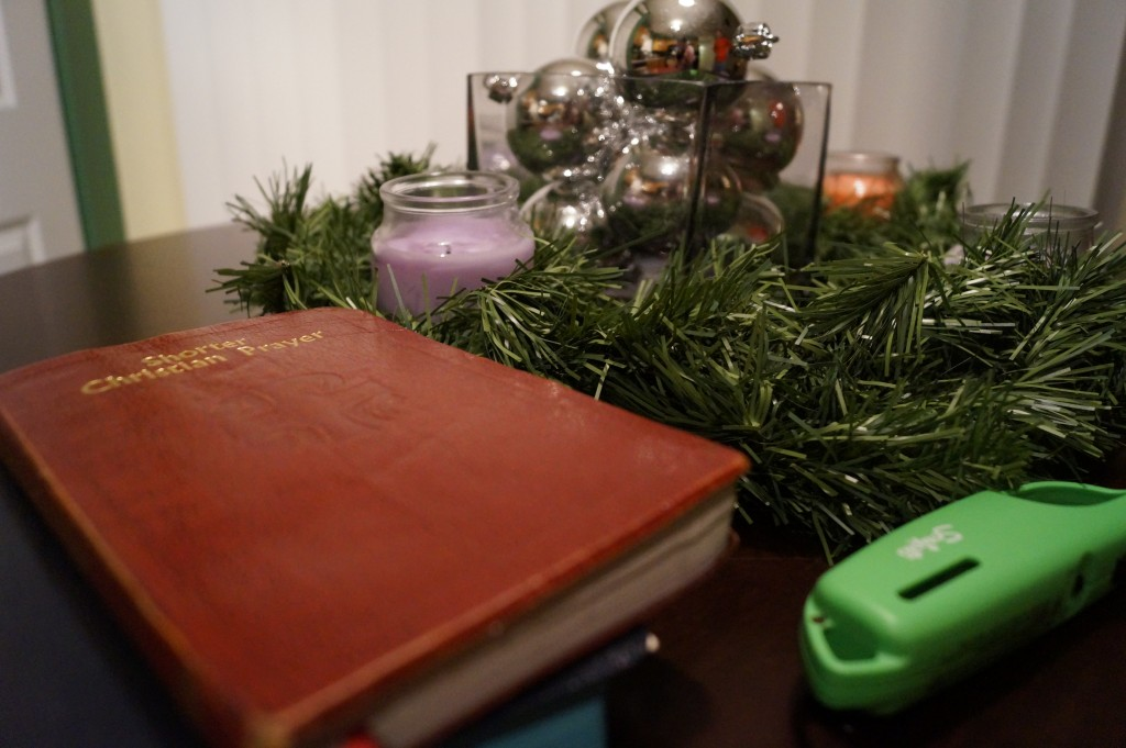 A homeade Advent Wreath sits on our kitchen table now. Nearby are books we are using to pray nightly devotions and prayers.